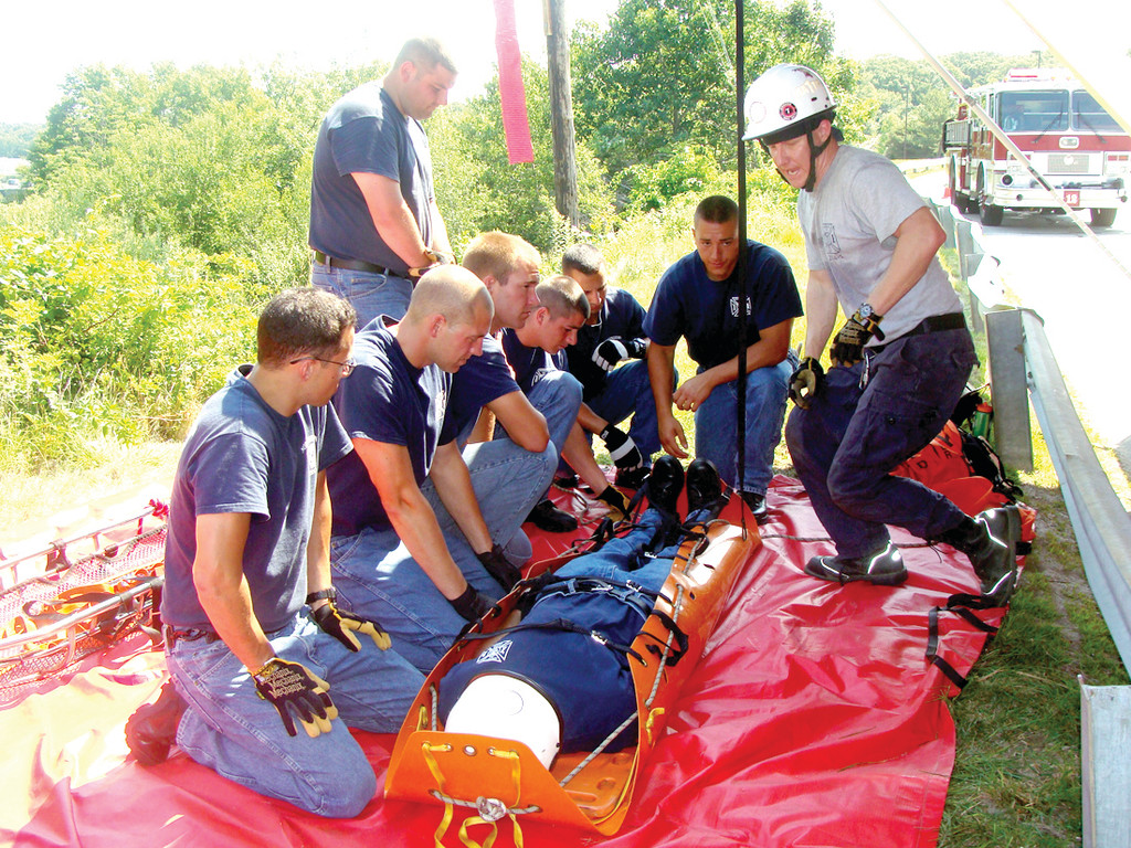 SAFETY FIRST: The vigorous and intense 18-week fire training program brought recruits outside Target on Bald Hill Road to practice a rescue on an embankment. The recruits practiced strapping and lifting a victim to safety.
