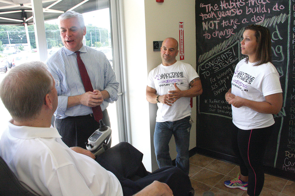 INSPIRATION: Rob LoBianco, owner of Anytime Fitness, and general manager Julie Lynch look on as Mayor Scott Avedisian and Congressman Jim Langevin arrive at the gym for an official ribbon cutting Saturday.