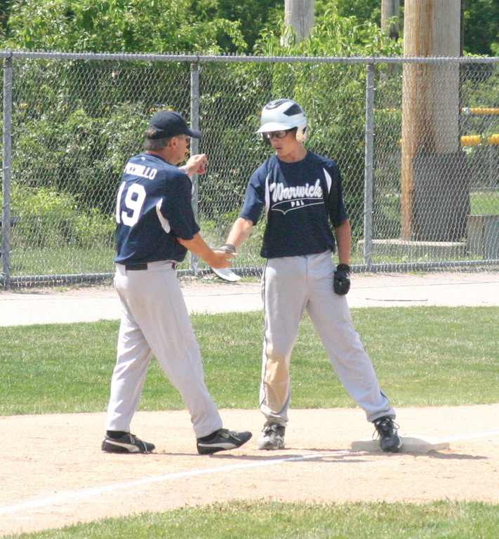 NICE JOB: Jacob Resendes high-fives manager Billy Piccirillo earlier in the tournament.