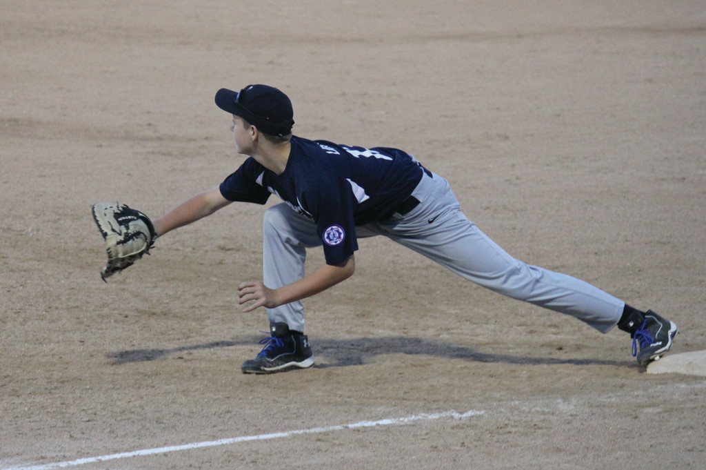 Jake Langevin stretches to reach a throw at first base.