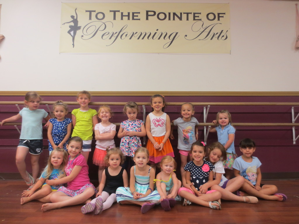 Taking a break from their recital preparations, a group of would-be ballerinas happily pose for a photo at To The Pointe of Performing Arts studio in Cranston.