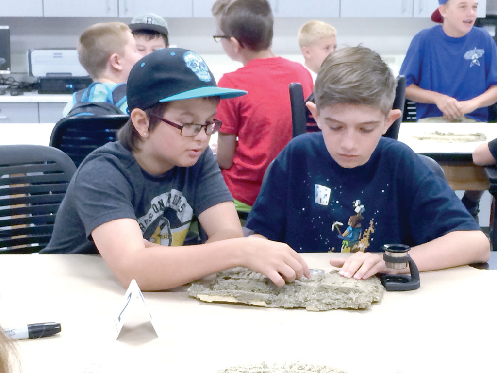SIZE SIX FOR SURE: Michael and Logan work together to identify the size and model of shoe prints to figure out whether a boy or girl was wearing it. At NEIT�s forensic lab the campers for the Leadership Camp got to explore a mock crime scene and then evaluate evidence.