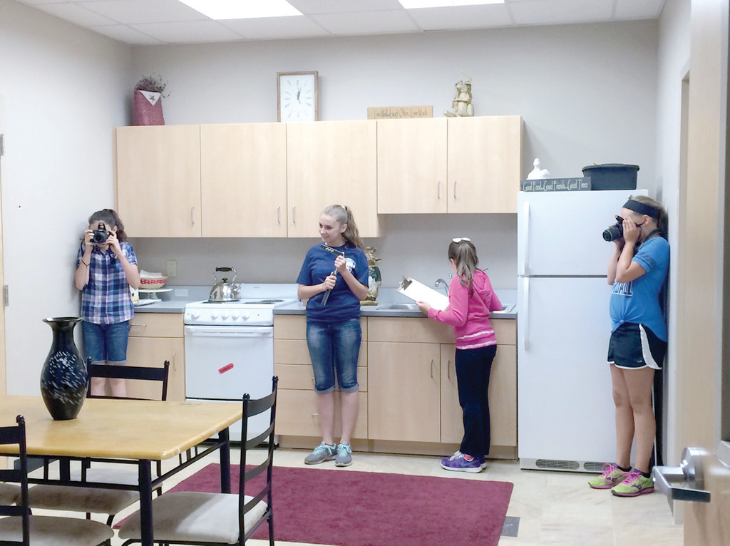 WHODUNIT? In a mock crime scene at the NETECH forensic labs, Hannah French, Daphne Eckert, Mackenzie Manning and Olivia Gilbert record every detail with rulers, cameras and a notepad. Each girl had her own roles from photographer to note taker.