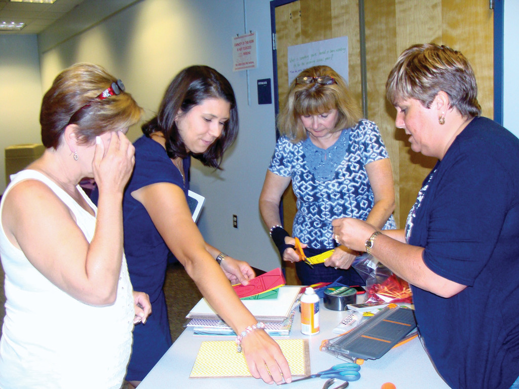 CRAFTS: Lisa Leito, Melissa Colangelo and Patti Shanley take instructions from Amy Dolan, one of the original teachers to begin Create and Collaborate. Together they are making homemade white boards that double as clipboards.