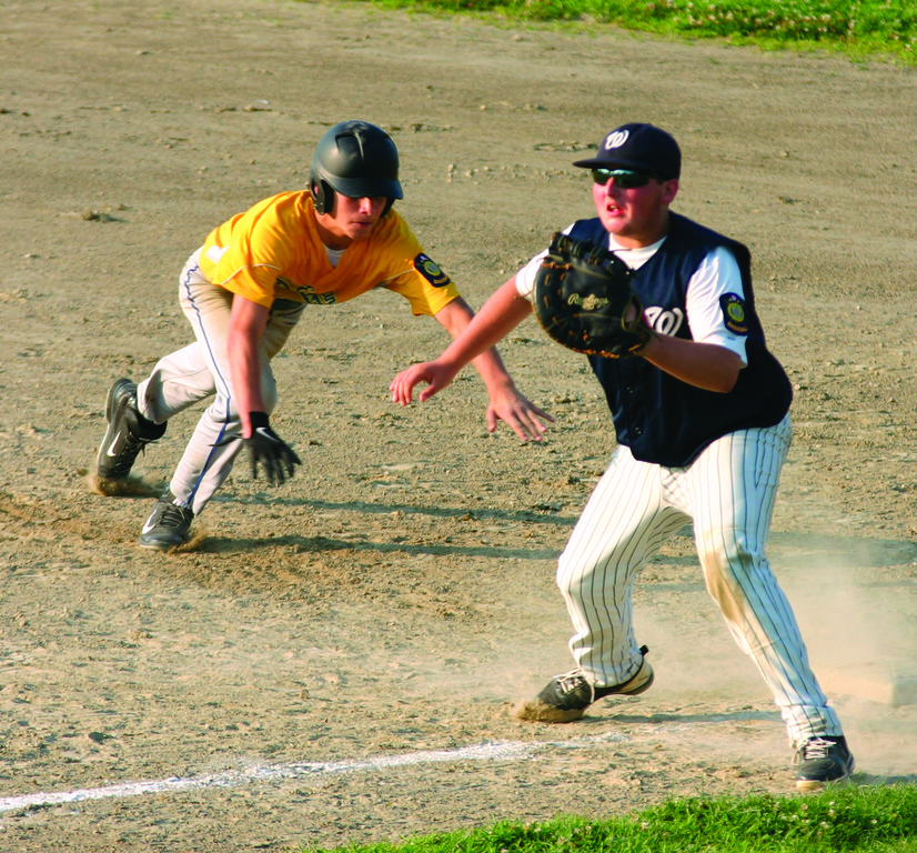 THROW BEHIND: PAL�s Bobby Garceau waits for a pickoff throw at first base as NEFL�s Dan Pratt slides back to first base.