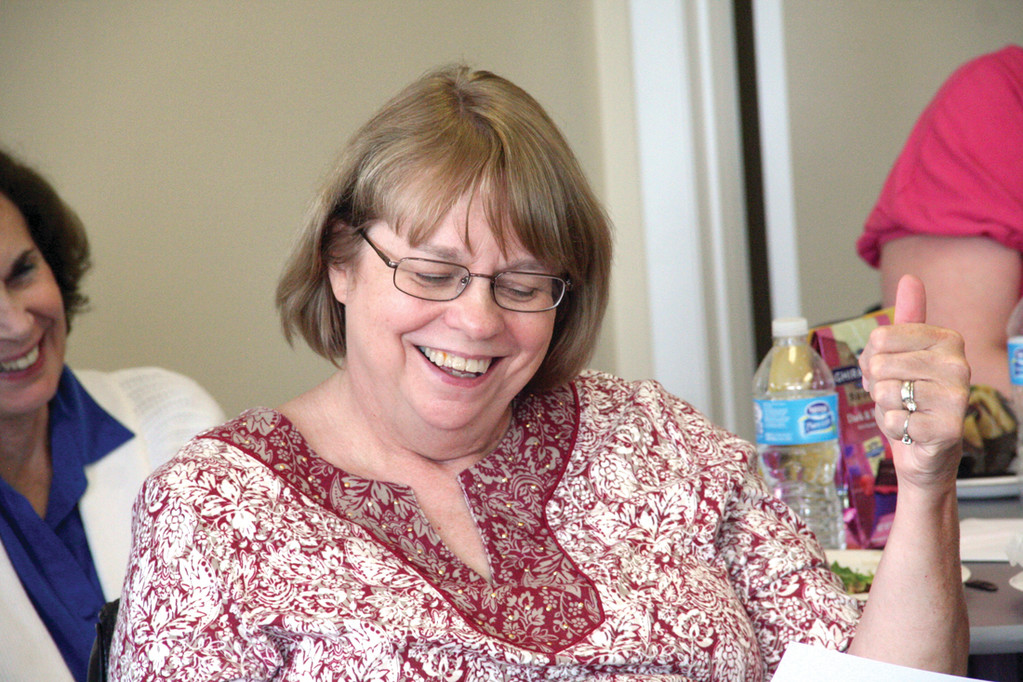 A DIFFERENT NEWSLETTER: Susan Eleoff, who retired Thursday from the Ocean State Center for Independent Living (OSCIL), gets a laugh from a mock newsletter produced by her co-workers.