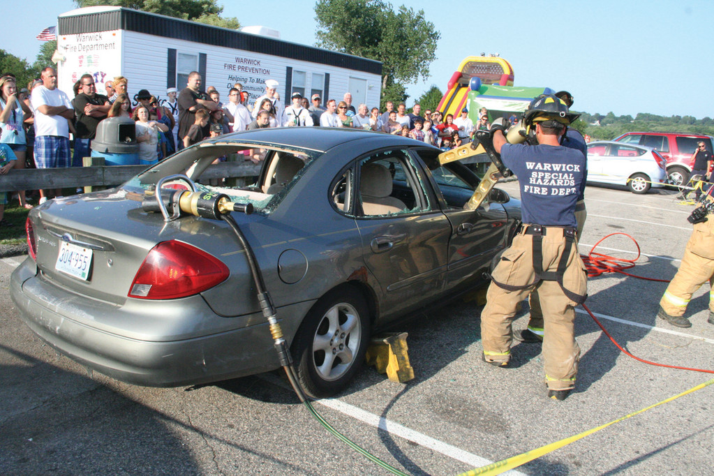 QUICK WORK: A 3-man crew of Warwick firefighters, using the jaws of life, demonstrated how they would save people trapped in a vehicle.