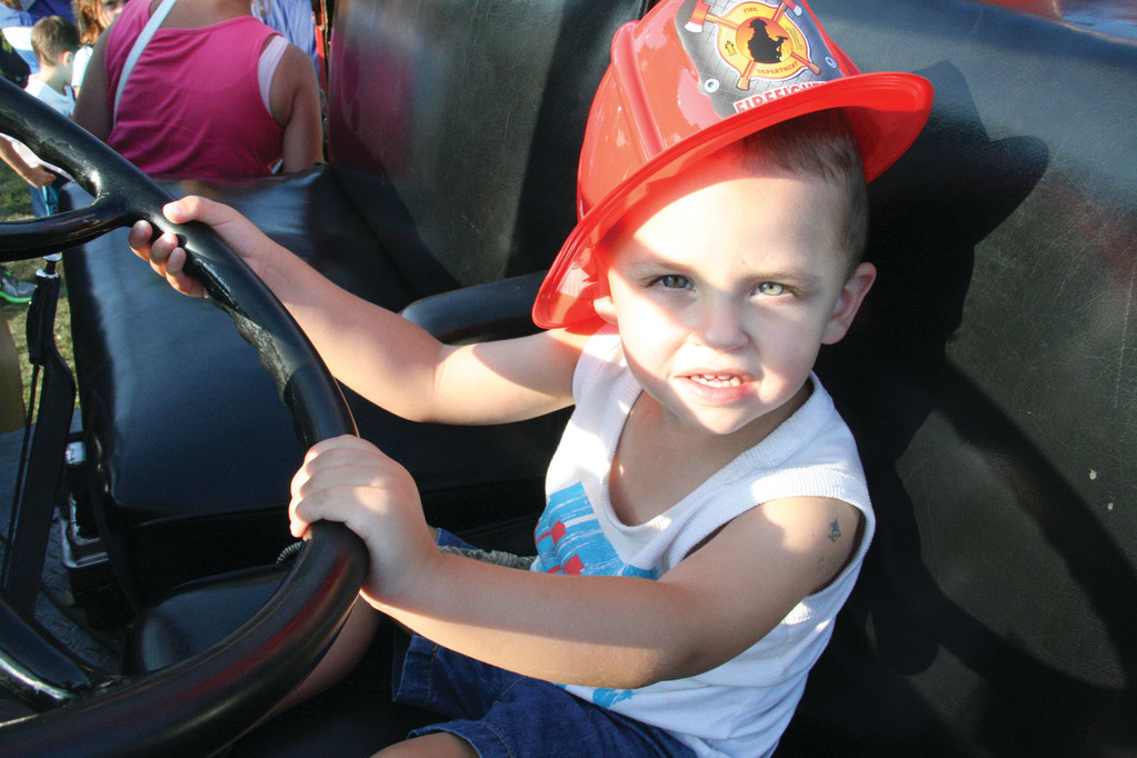 READY TO DRIVE: Ayden Hudson, son of Larissa and Jared Hudson, was appropriately fitted with a firefighter's helmet for his time behind the wheel of a vintage truck.