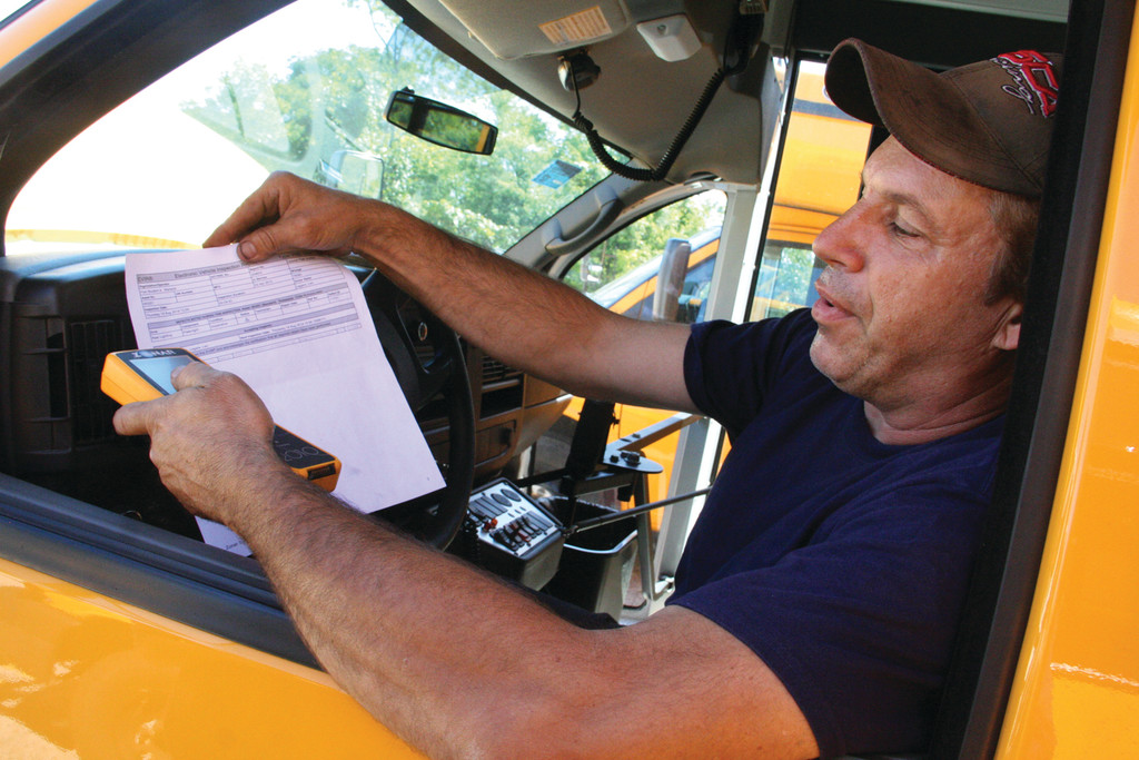 KEEP TRACK: Fred Cordeiro, mechanic and technician for First Student bus company, runs a diagnostics test on the bus Zonar system in preparation for the first day of school next Wednesday. The system that requires each driver to log in with an identity card tells headquarters where the bus is at what time as well as how fast it is driving. Further, he explained, it provides a read-out of the bus and whether it is mechanically operating properly at the beginning and end of the day.
