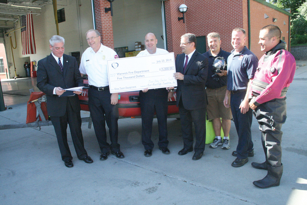 BOOST TO DIVE TEAM Mayor Scott Avedisian stands next to Chief Edmund Armstrong and Assistant Chief James McLaughlin, who holds a $5,000 check given by the Ocean State Charities Trust to aid in the purchasing of new dive equipment. Dr. Joseph Spinale stands along side Rescue Lt. Gary Pelliccio, Lt. Tom Brady and Lt. Bill Wilson.