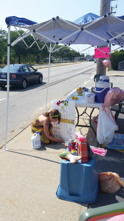Megan Medeiros readies her lemonade stand, which she set up last week in the parking lot at Hair Odyssey on Post Road to raise funds and collect items for the Warwick Animal Shelter.