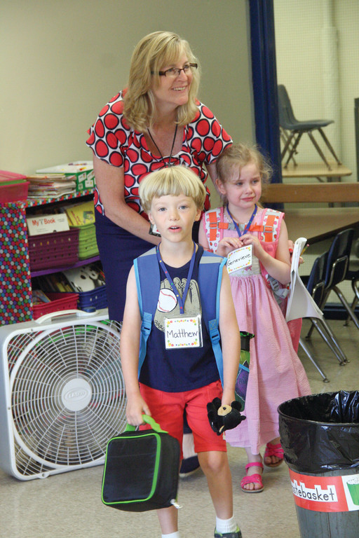 JOINING THE CLASS: Warwick Neck Principal Patricia Cousineau guides kindergartners Matthew Bailey and Genevieve Roy to their class.
