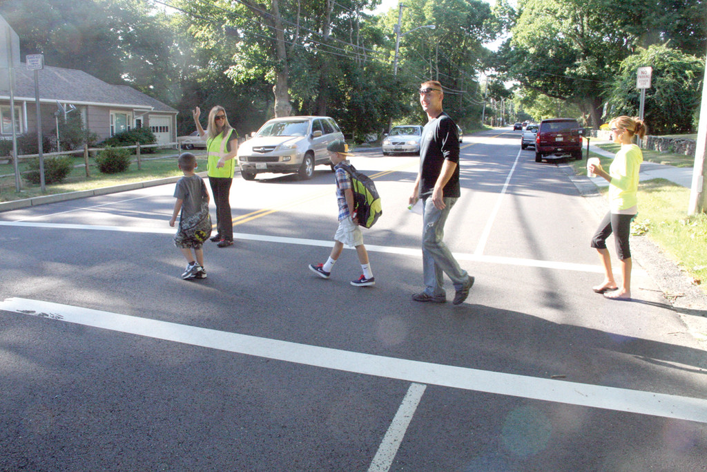 SAFE PASSAGE: Crossing guard Robin DeFelice halts traffic on Warwick Neck Avenue as parents and their children cross to Warwick Neck School yesterday morning.