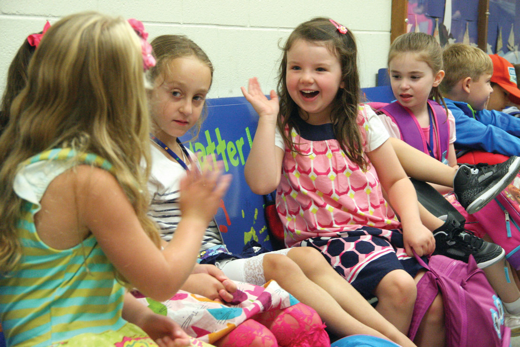 FINDING FRIENDS: Lilly Pigeon is delighted to find a friend, Catherine DeLuca, among those kindergarteners waiting to be ushered to their room at Warwick Neck. The girls met at St. Kevin School last year.