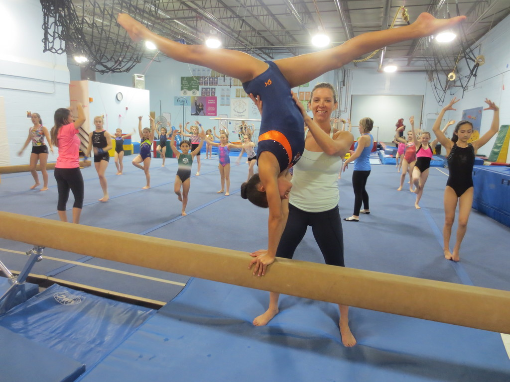 "Owner Shannon Cornicelli spots thirteen year old gymnast Danae Metts as she does a ""back walk-over"" on the balance beam at Dream Big Academy."
