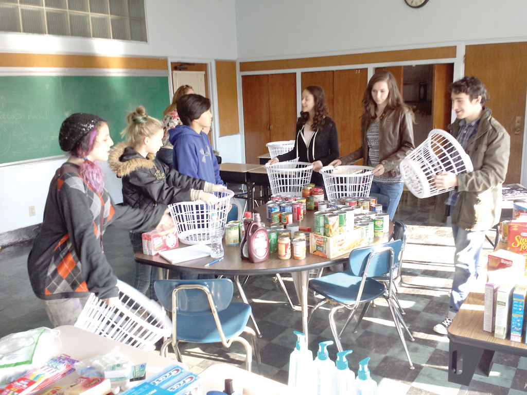 SERVICE PROJECT: The teen group from EnrichRI's statewide home school program gathered together Thursday to divvy up the food items collected for their Thanksgiving baskets.
