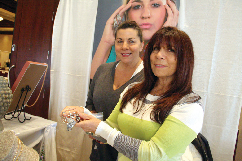 OF MIND, BODY AND SPIRIT: Diana Lozowski and her sister, Deborah Hutton, set up the Zen by Alexa Rae booth at Saturday's event at the Crowne Plaza. Diana's daughter, Alexa Rae, who is pictured on the poster, founded the Johnston company that produced a charm especially for the event featuring the outline of a Buddhist head and temple to symbolize the coming together of mind, body and spirit. The company works closely with non-profits in developing jewelry that will assist them in fundraising campaigns.
