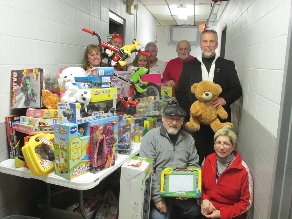COLOSSAL COLLECTION: Mark Eaton (standing right), Exalted Ruler of the Tri-City Elks on West Shore Road, holds a teddy bear that was among over 250 toys that Lodge 14 collected Saturday evening at its first-ever Holiday Cheer Program. Eaton is joined by (from left) Elks Lori Eaton, Chris Carcieri, Diane Bannister Duquette, Bob Beaudry and Dick and Donna Warner.