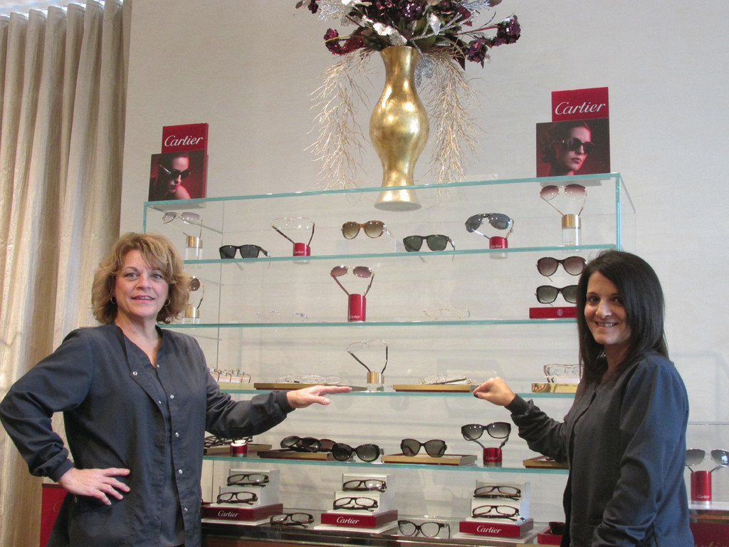 PROUD SPONSOR: OPTX Rhode Island staffers Belinda Moretti, left, and Kim Ventura show off the Cartier display located in the Johnston-based company's unique boutique gallery.