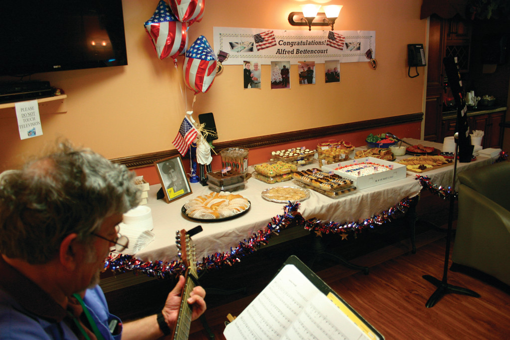 LOVE OF COUNTRY: Patriotic songs are performed as refreshments and photos fill a table prior to Monday's ceremony.
