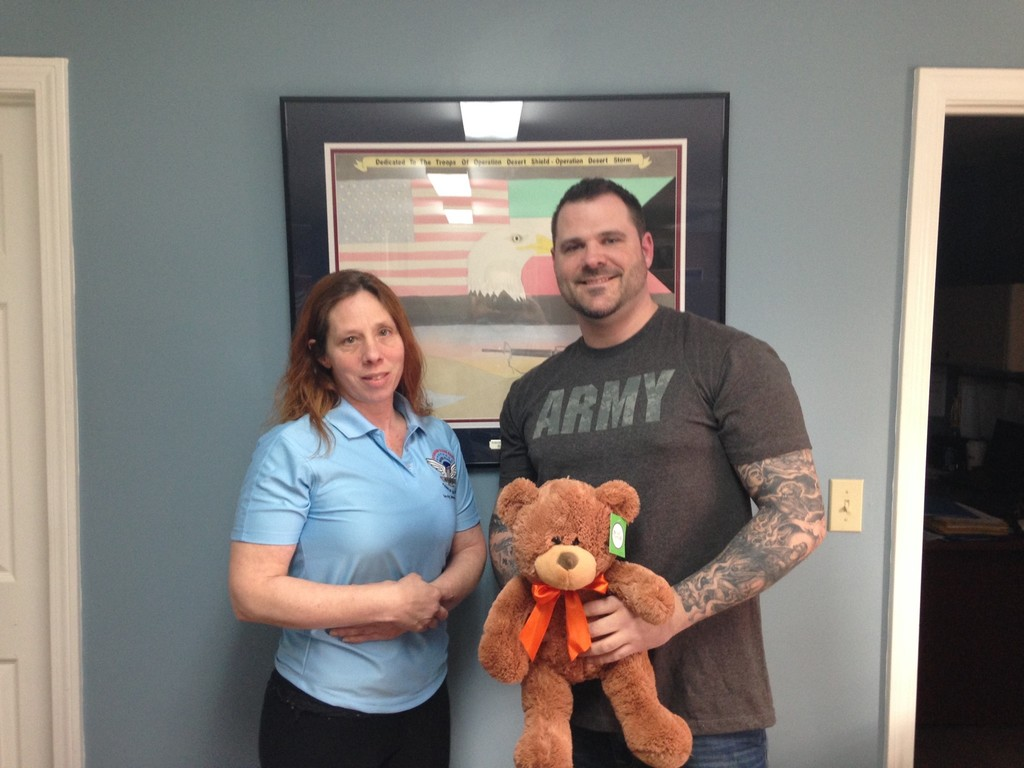 A TOY BEAR FOR HIS SON: Sherry Elderkin, Operation Stand Down's Transitional Housing and Special Project's Manager gave a stuffed bear, Legos, and other toys to Jason Boulay for his son, Liam. Jason and Liam lost all their possessions and their home when fire consumed their building at Westgate Condominiums.