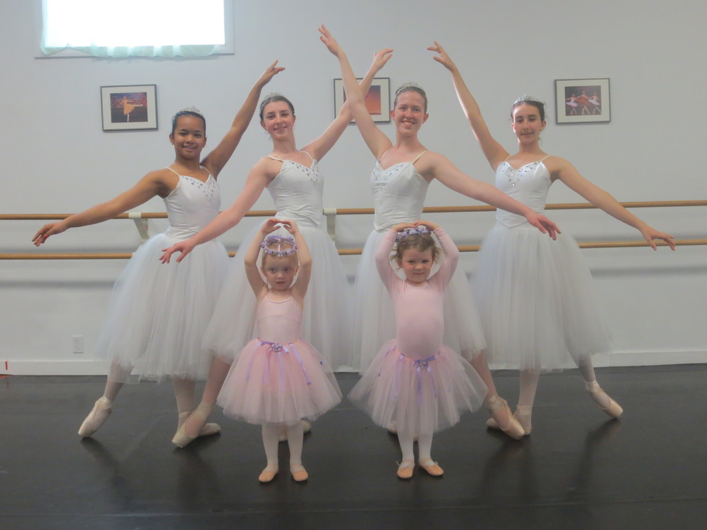 A bevy of beautiful ballerinas, ages 16 – 18, take a graceful stance behind a group of tutu-clad 3-5 year old protégés at the Heritage Ballet studio in Lincoln.