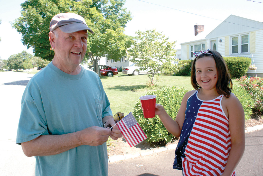 CUSTOMER SATISFACTION: Olivia VanPatten hands a cup of lemonade to her neighbor, the Rev. Francis O'Hara, a retired priest from St. Kevin's Church who stopped by to support the cause.