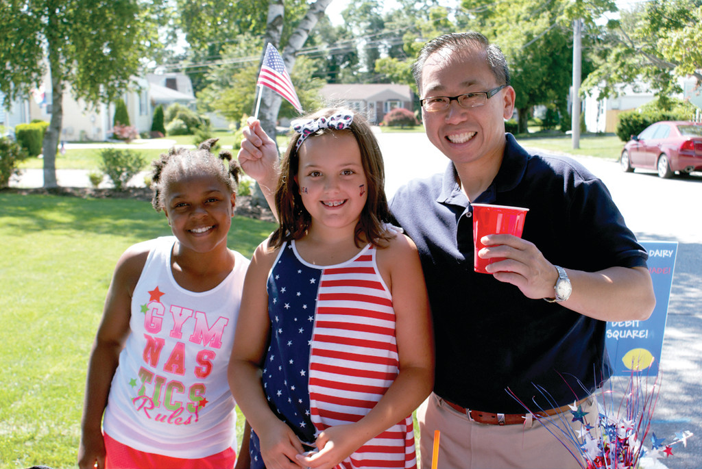 MAYORIAL SUPPORT: Supporting Olivia VanPatten's dream of a lemonade stand to benefit Pets for Patriots was Mayor Allan Fung, who enjoyed the blueberry lemonade very much. He is pictured with Amani Jackson and Olivia VanPatten as he waves his American flag, which the girls gave out with every purchase.