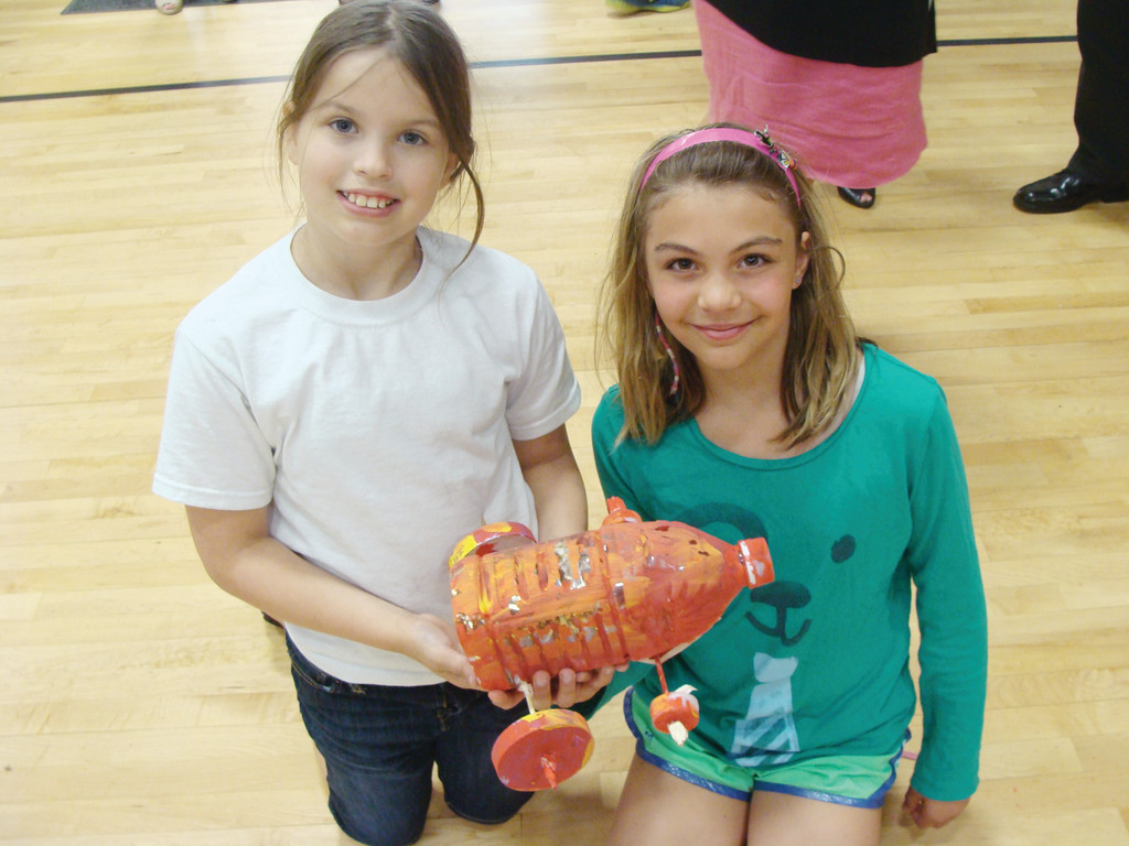 TEAMWORK: Lily Soares (left) and Brenna Maine hold up their race car made out of recycled materials. They both said they love the camp. All the students had to work with a partner to design and engineer a miniature racecar.