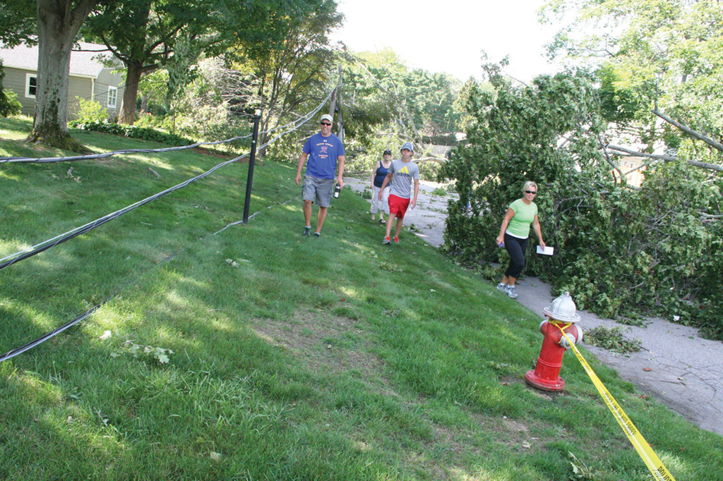 LAND OF TOPPLED TREES: Paul, Kim and Corey Olson were joined by Tom and Sandy Ey as they used Wauregan Drive, which was closed to vehicular traffic, to check on others living in Governor Francis Farms.