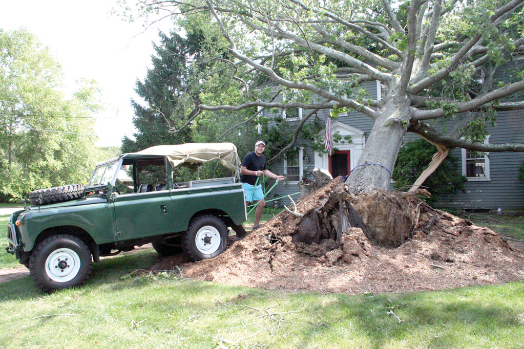 SOMETIMES LAUGHTER IS BEST: Grant Pilkington of Squantum Drive couldn't resist tying a strap between the gigantic tree that crashed on his parent's home and the 1970 Land Rover. Pilkington said he was doing his part to clean up after the storm. He got lots of stares and laughs.