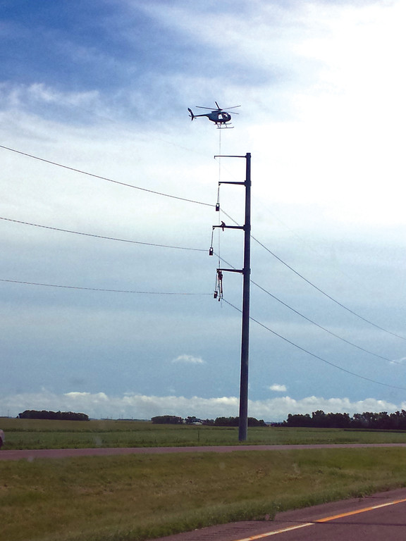 THE THINGS YOU SEE: We were continually fascinated by random crazy things we saw on this trip, such as this utility pole worker, lowered down to the middle of the pole by helicopter, where he sat and did his work as we drove by.
