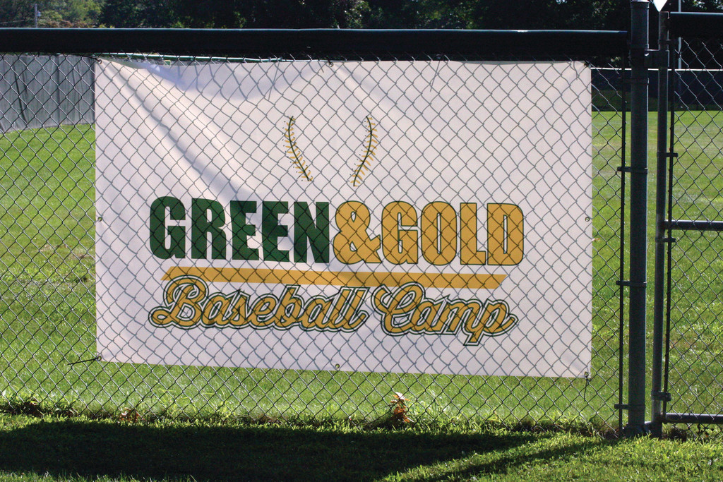 THE START OF A TRADITION: The Green and Gold Baseball Camp banner was draped on the fence at Hendricken's Ray Pepin Field last week for the first time ever.