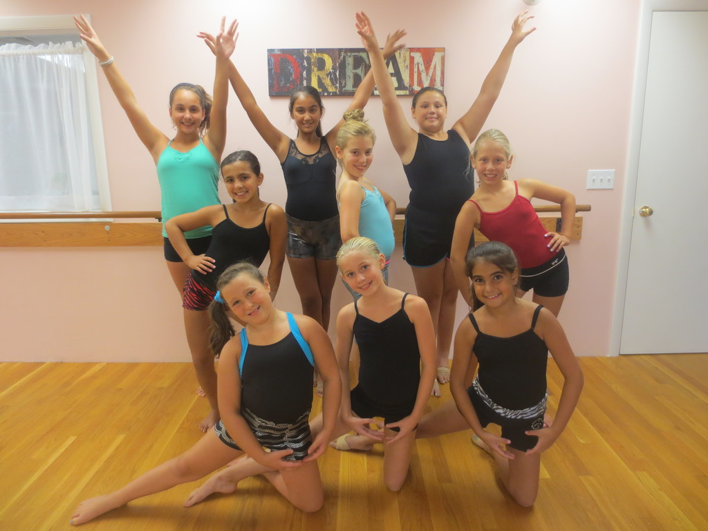 A joyful and smiling group of dancers, ages 9-11, take a short break from their dance practice to pose for a graceful shot at the Jean DeLuca Dance Studio on Hartford Avenue.