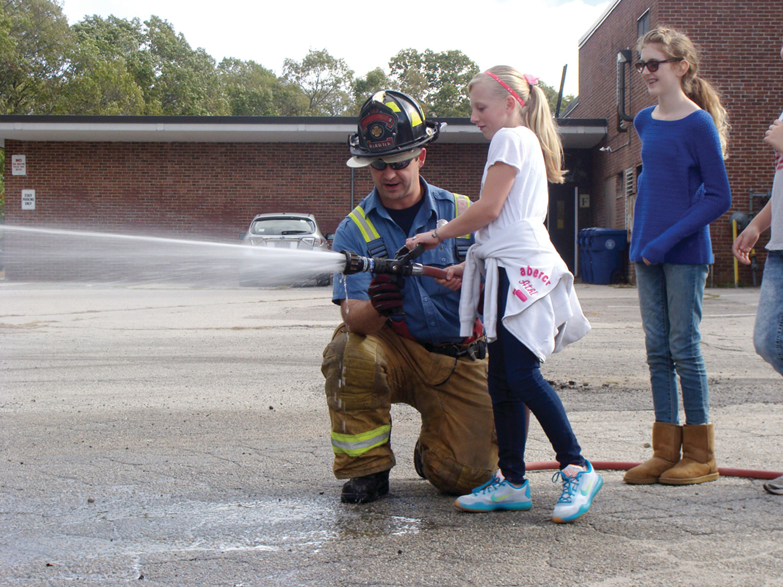 HOLD THE HOSE: Members of the Warwick Fire Department visited Holliman Elementary with two trucks on Wednesday afternoon for the Touch a Truck for a Buck fundraiser. Students learned about the different parts of a fire truck and were even able to use one of the hoses off the trucks with the help of a fireman.