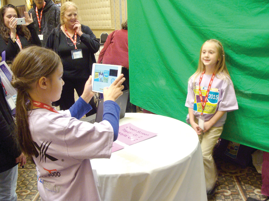 SAY CHEESE: Makayla Nava, left, takes a photo of Taylor Tatarian in front of a green screen.  Parents and educators from across the state visited Warwick Neck's exhibit where the students demonstrated how they used technology in their classrooms.