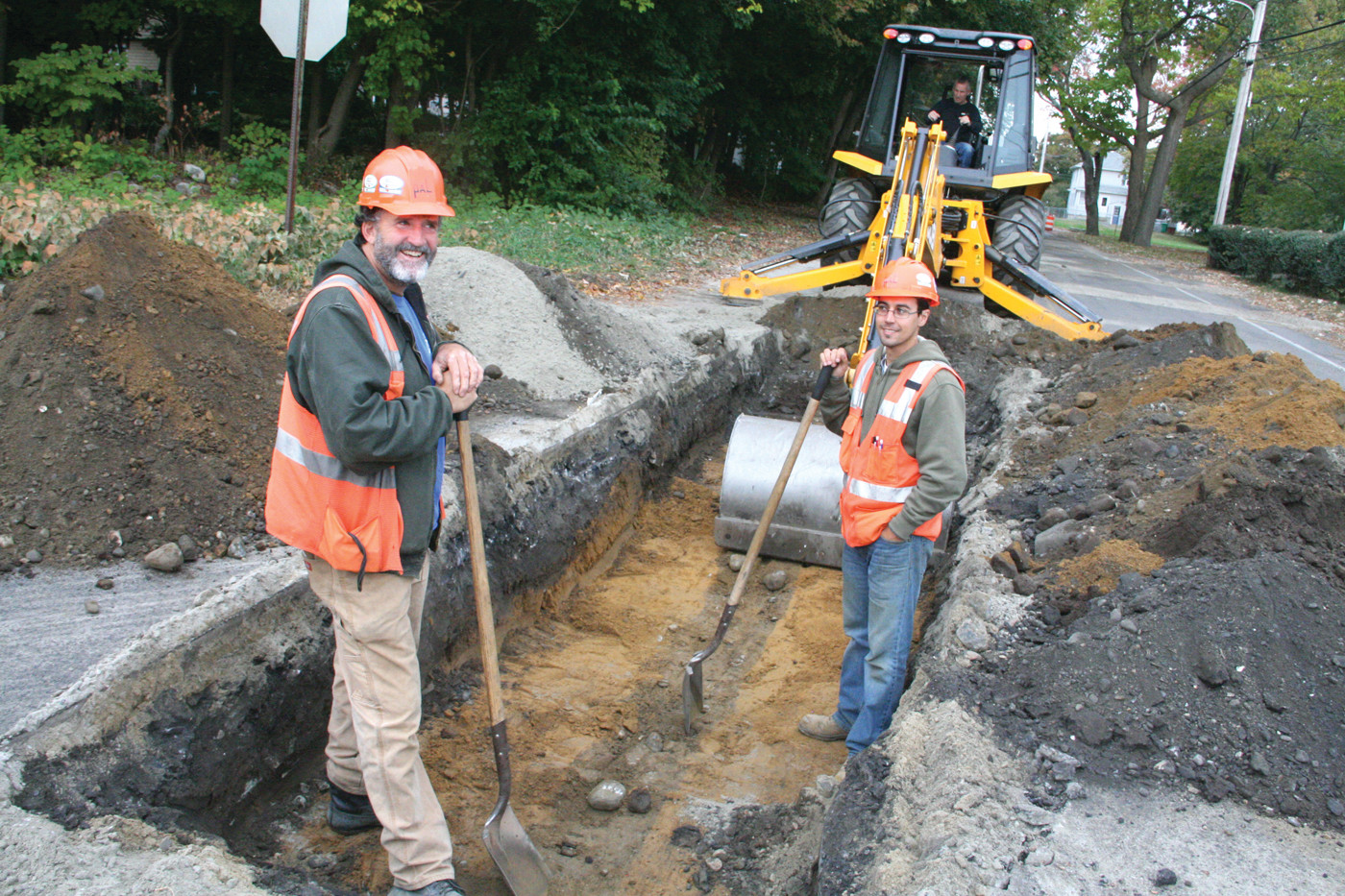 YOU NEVER KNOW WHAT YOU�LL FIND: Archaeologists Kirk Van Dyke and Alex Flick stand by as a flat bladed backhoe unearths section of Tidewater Drive in a survey of the trench to be used for a main sewer line.