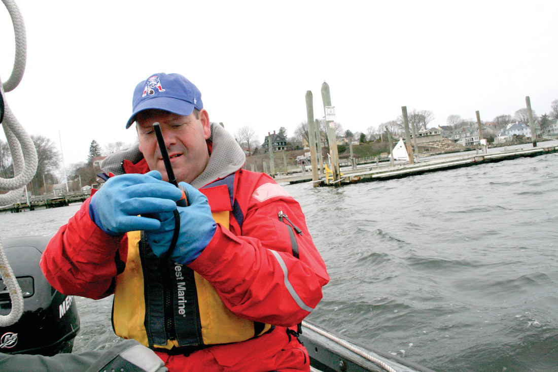 MAKING CONNECTIONS: Dennis Demers, who operates the chase boat and sets marks for the sailors, checks his radio connection with Malone on the committee boat.