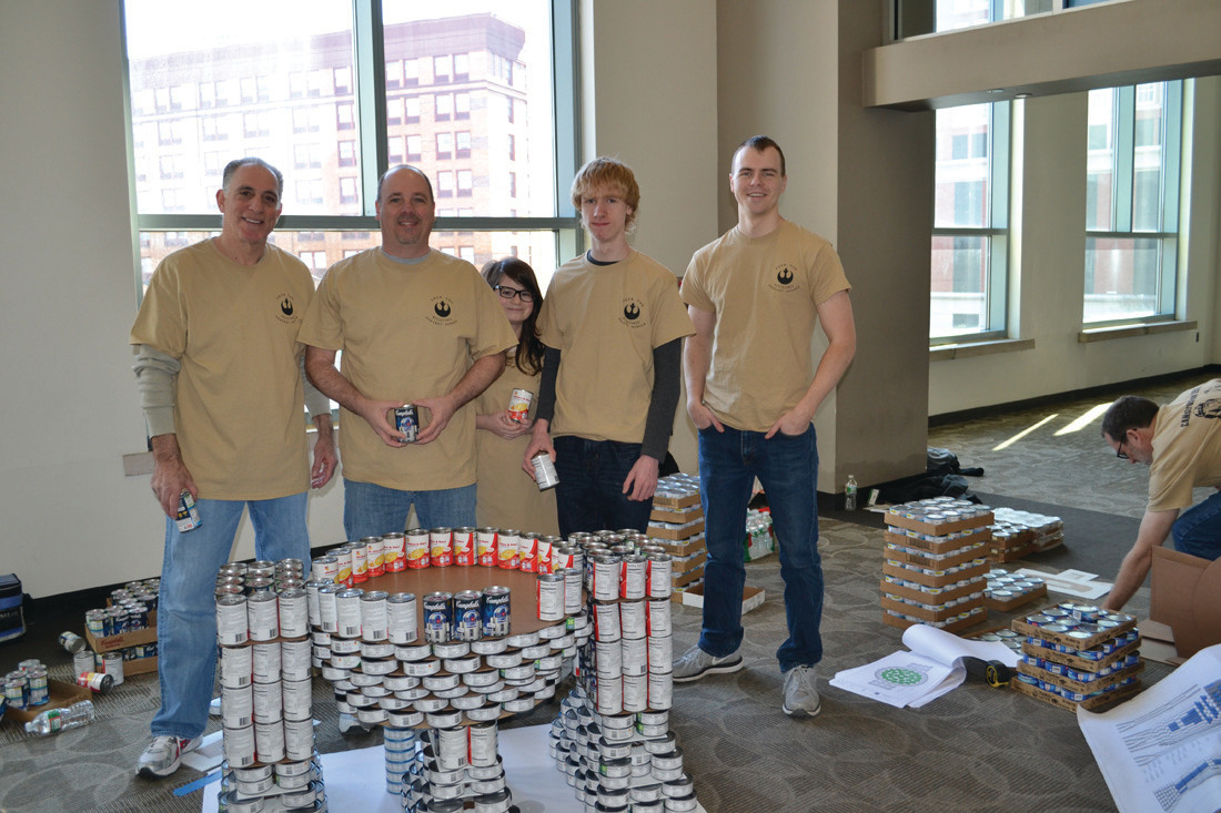 CRANSTON RESIDENTS were among those building the Saccoccio-DiPrete Engineering-H.V. Collins team's sculpture, which won the Best Meal award in the recent Canstruction RI event to benefit the RI Community Food Bank. Working on the R2-D2 part of their sculpture are, from left, Steve Guglielmo, a principal of Cranston-based Saccoccio Architects; Ron Stevenson with his children, Kate and Cole; and Jakob Cruikshank.