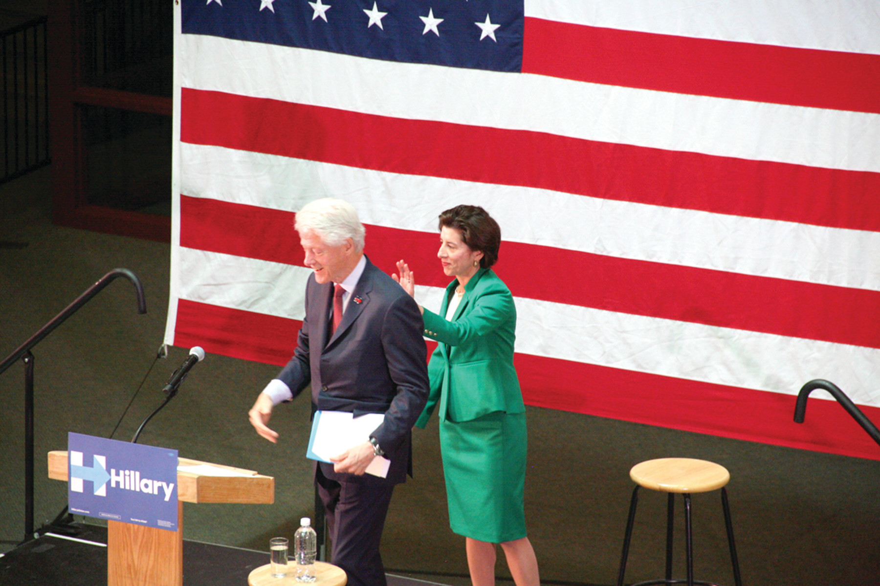 PAT ON THE BACK: Gov. Raimondo welcomes President Bill Clinton to the podium at the Knight Campus of CCRI.