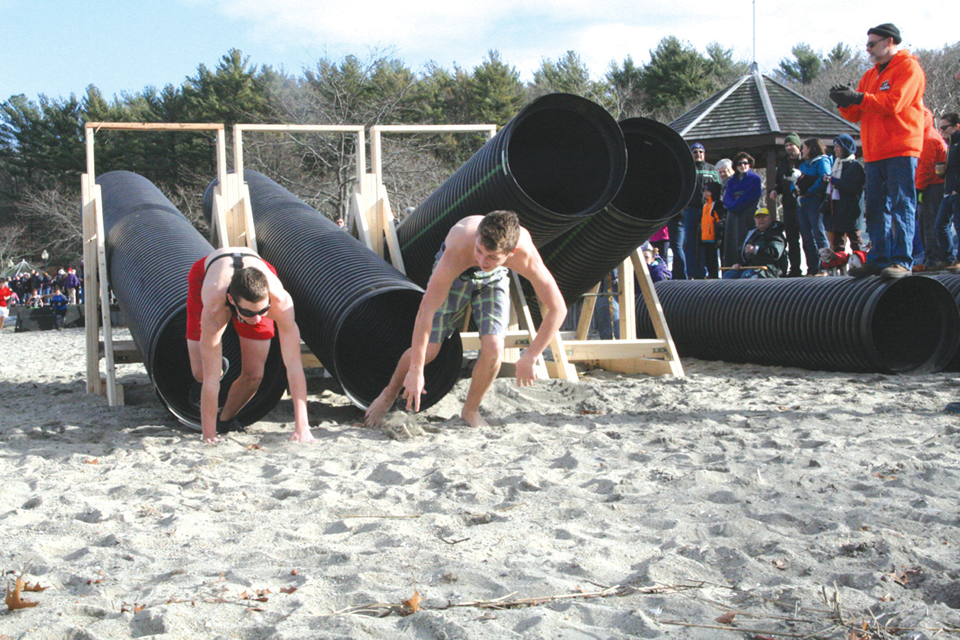 NEW YEAR: Participants in the obstaplunge navigate the teeter-totter at the Frozen Clam Dip to benefit the Rhode Island Mentoring Partnership held at Goddard Park this year. Lynn Hall from BoldRDash debuted the tunnel obstacle at the event.
