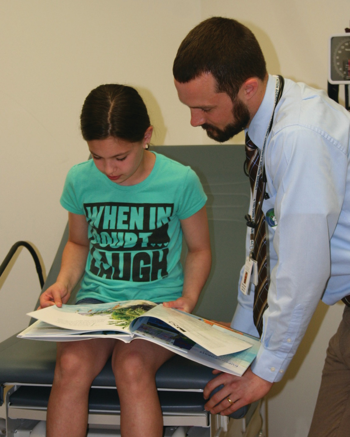 REACH OUT AND READ: Tri-Town Health Center Medica Director Dr. Matt Malek, right, reads along with Addison Papagolos, who attended the Reach Out and Read Rhode Island story time on May 25 in North Providence.