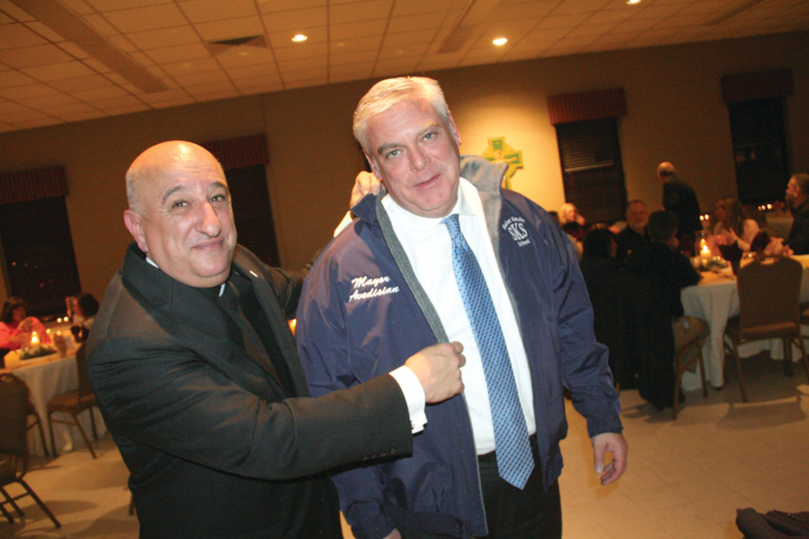 JUST WHAT'S NEEDED ON A SNOWY NIGHT: Father Robert Marciano, pastor of St. Kevin Church, presented Mayor Scott Avedisian with a jacket in appreciation of the mayor's efforts on behalf of St. Kevin School and its students.