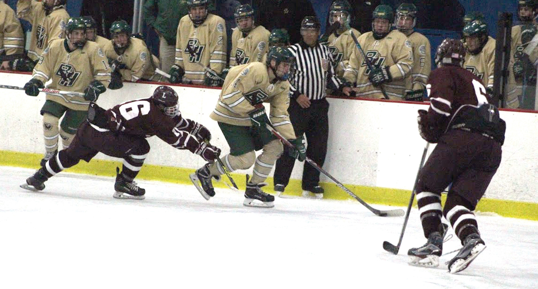 AGAINST THE BOARDS: Michael DiMascolo (center) works the puck up the ice for Hendricken.