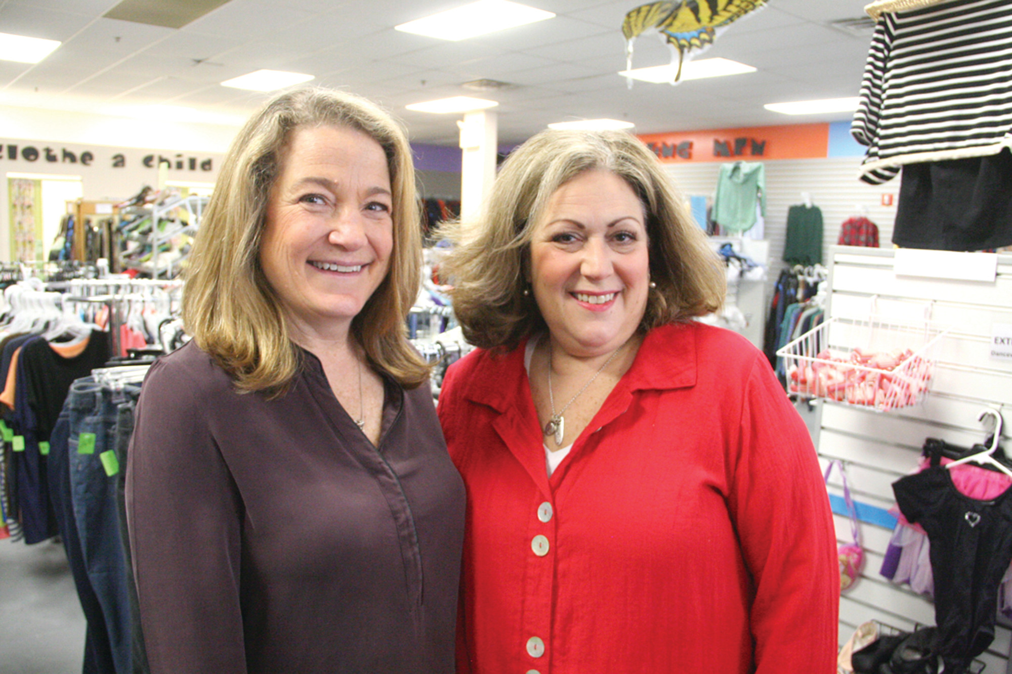 FRIENDS SINCE LAW SCHOOL: Marianne Baldwin and Eva Mancuso, co-founders of Clothes to Kids RI share a laugh in the store. On a recent weekend the pair visited numerous Walmarts to take advantage of a $5 special on kids' sneakers.