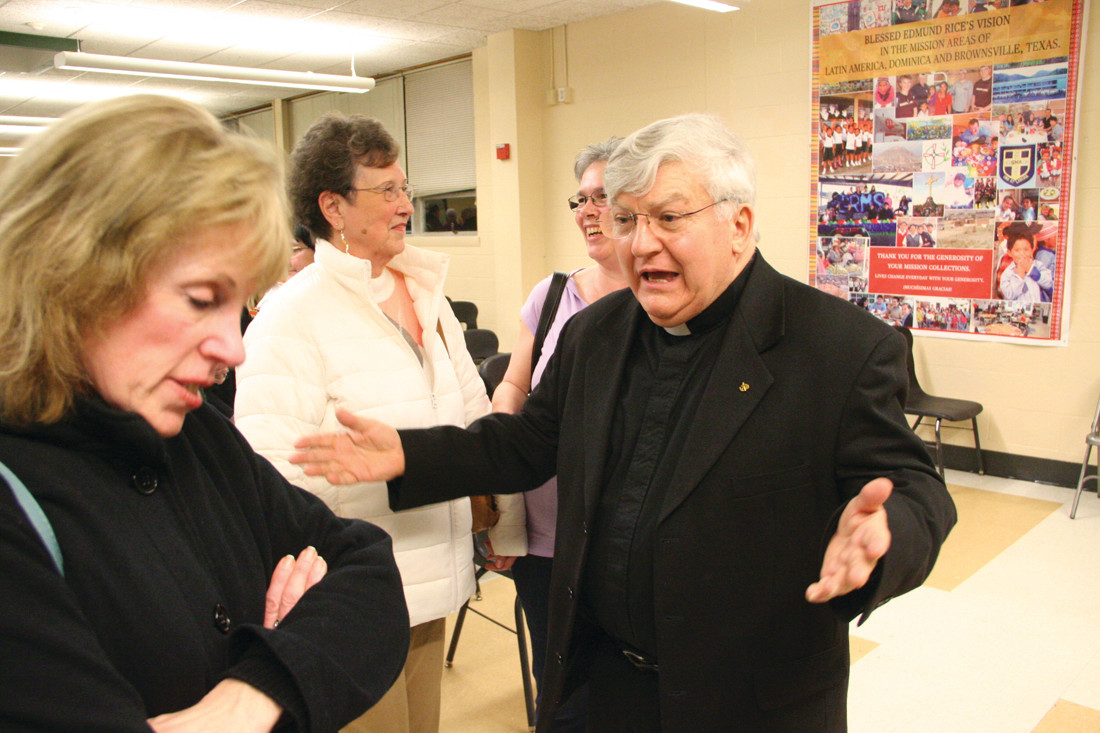 "WHAT WILL THE FUTURE BRING: St. Benedict parishioners talk with pastor Father Roland Simoneau following the diocesan ""town meeting"" Wednesday night."