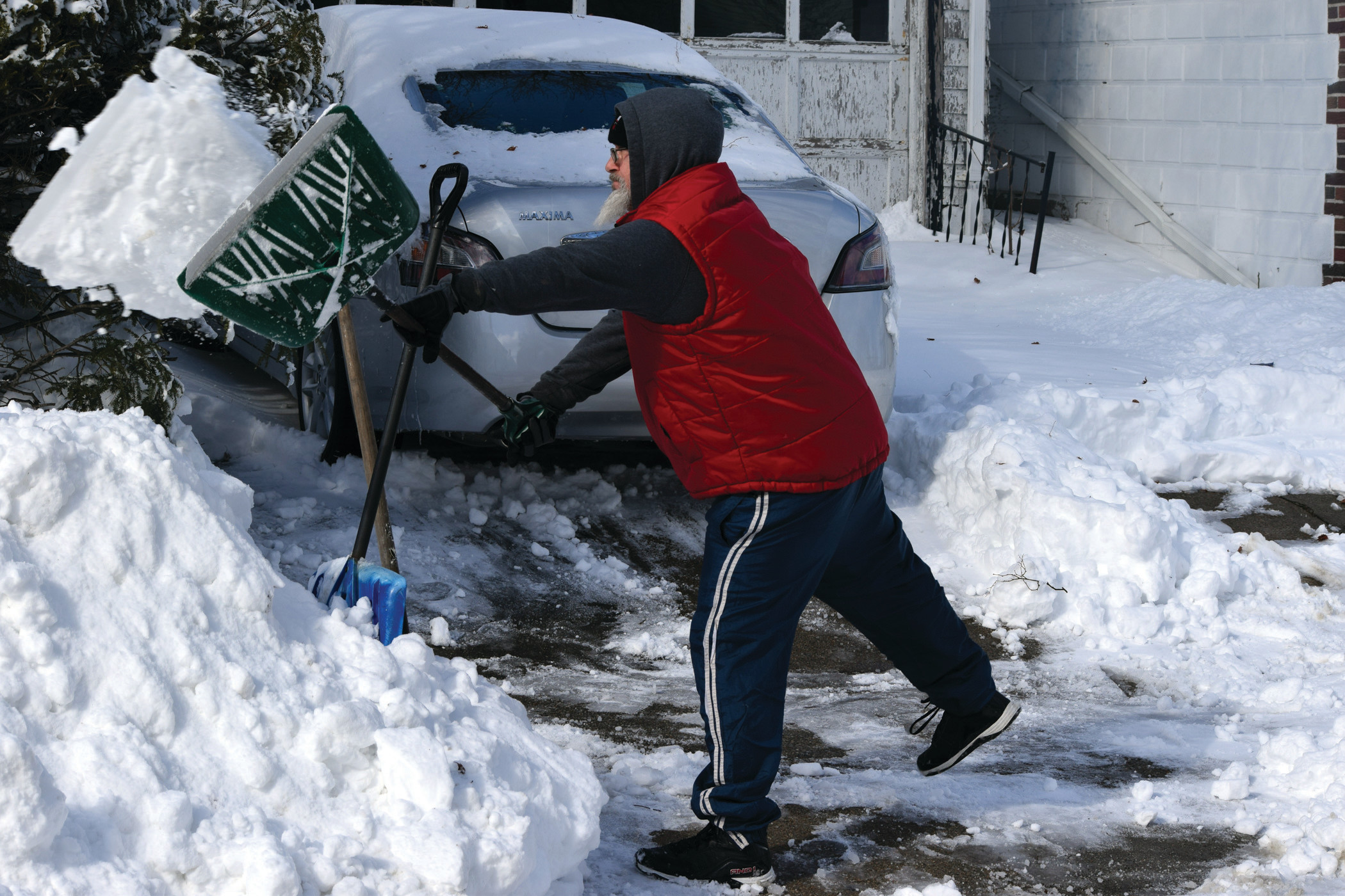 BATTLING WINTER: Kirk Wilcox, 55, shovels out his daughter's driveway on Friday morning. Thursday's blizzard hit Cranston with 12 inches of snow.