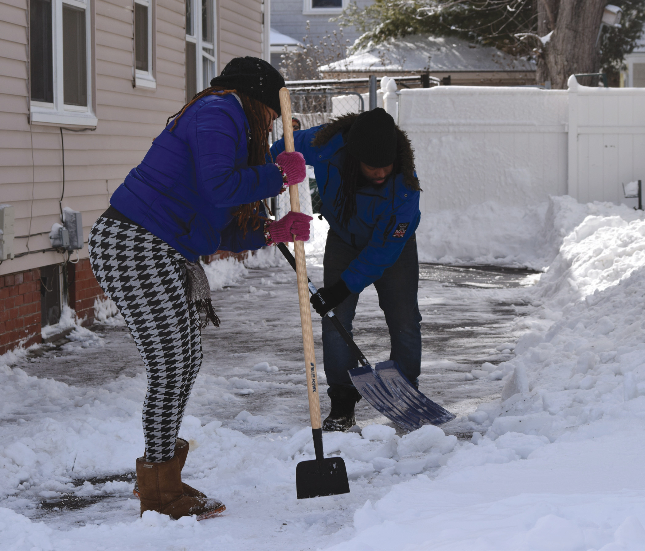 CHIPPING AWAY: Joyce Dragon and Booz Derogene work to clear up a sheet of ice under the snow.