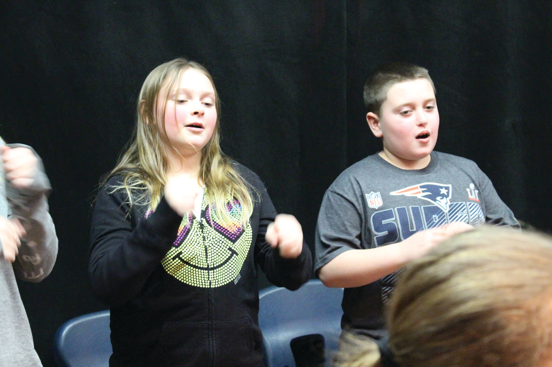 GETTING THEM TO SING: Music teacher Susan Brunelle coaches Holliman School fifth graders in the singing of a round.