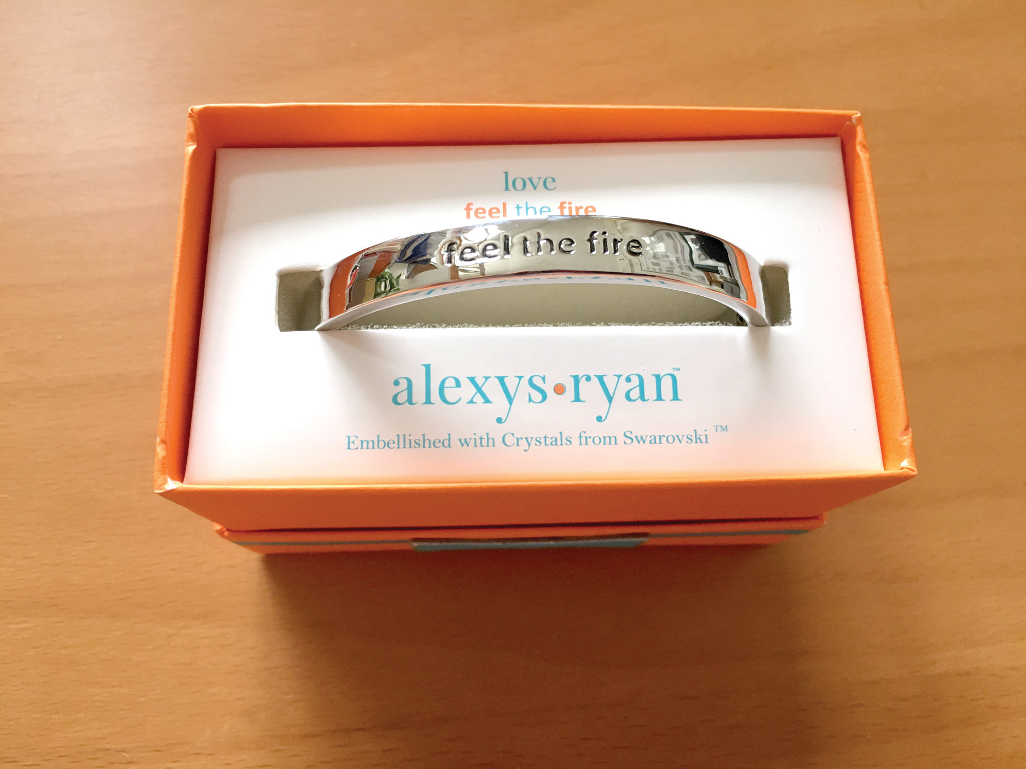 "FEEL THE FIRE:"" The ""love"" bracelet reads ""feel the fire"" on one side and ""love"" on the other."